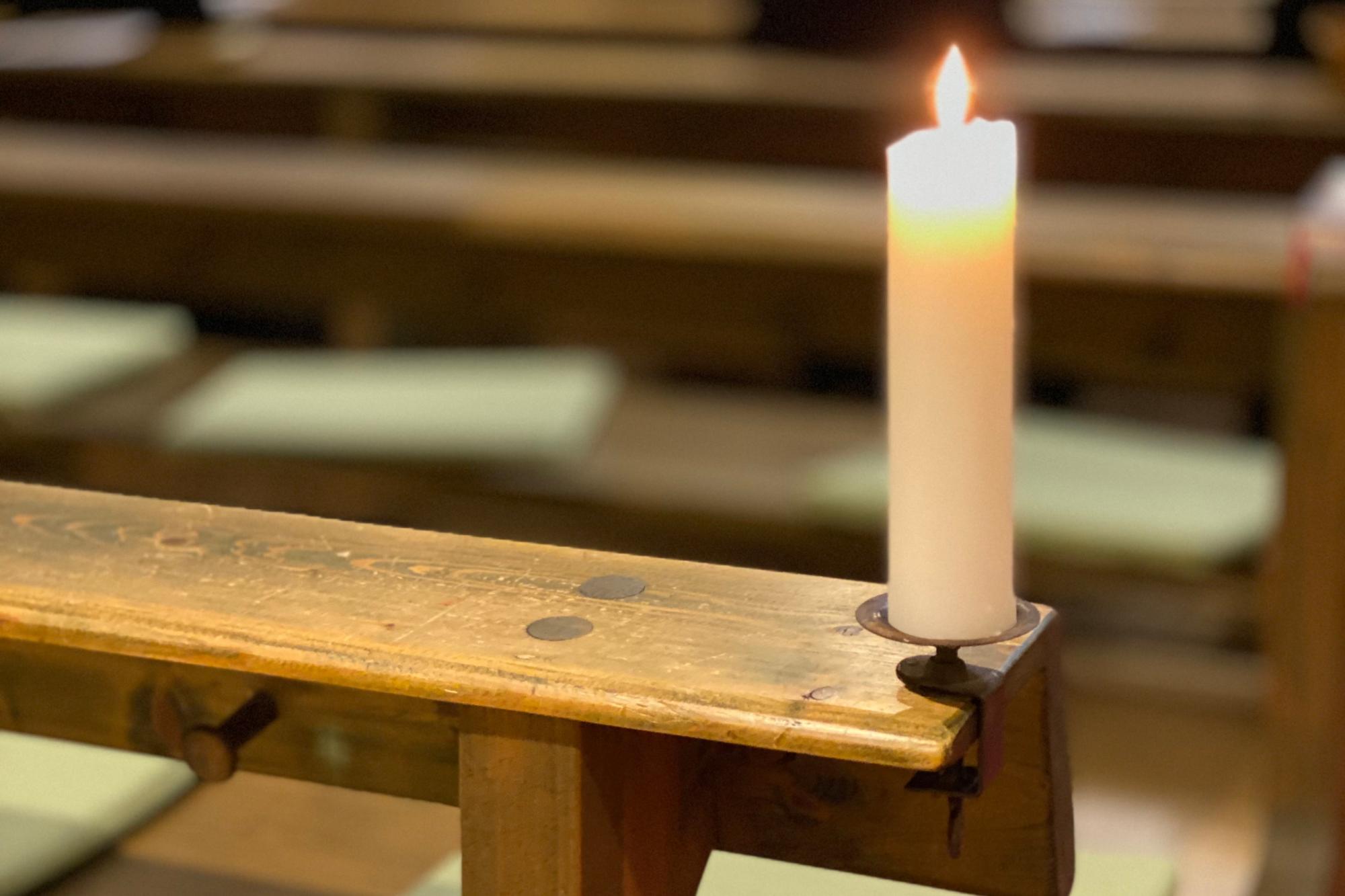 Kerze auf Kirchenbank