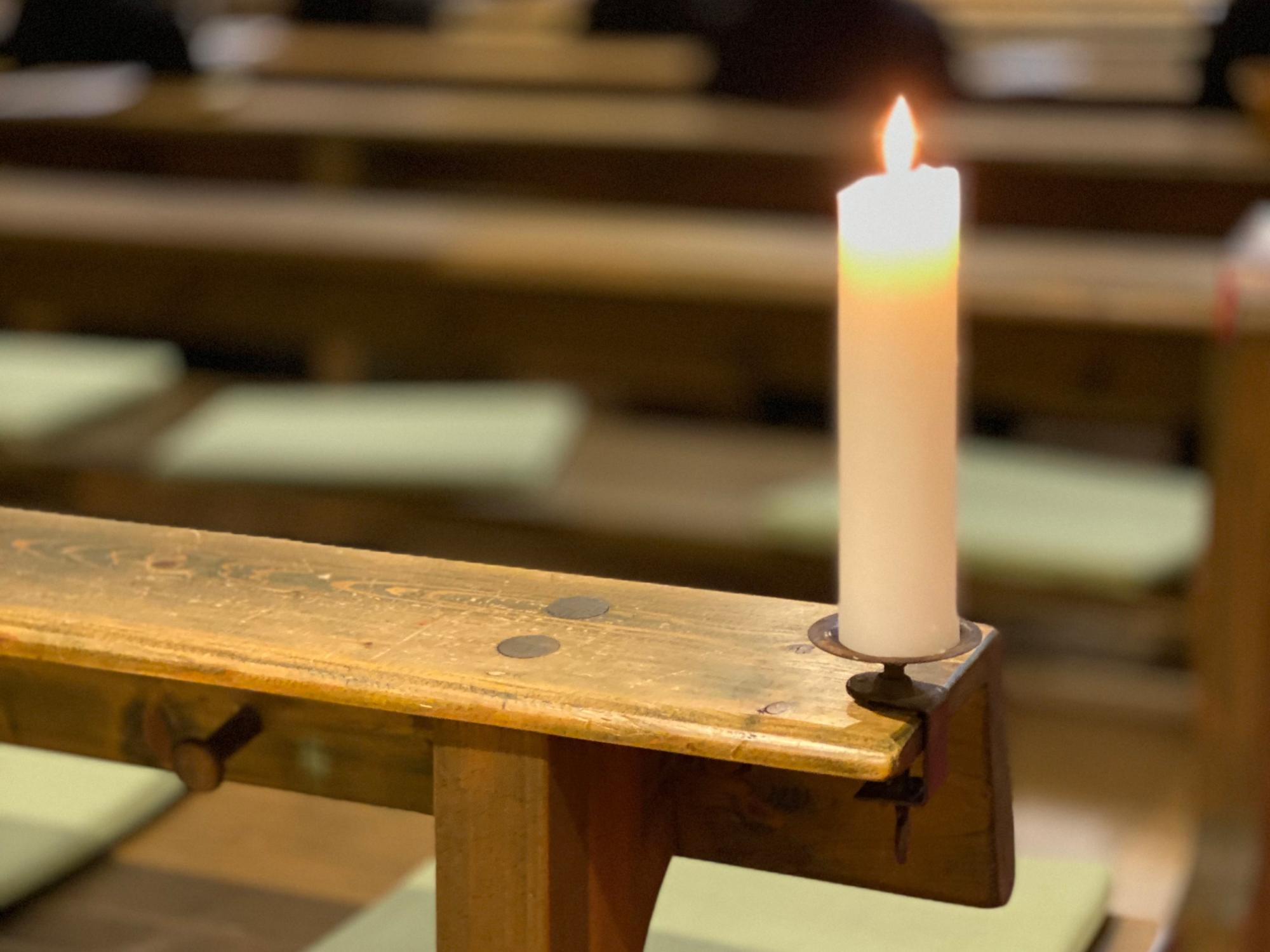 Kerze auf Kirchenbank (c) Bild: Martin Battert In: Pfarrbriefservice.de